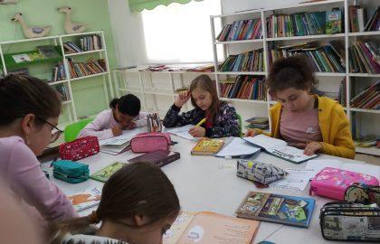 במסגרת קידום פרויקט קריאה המורה שושי יושבת עם התלמידות בספריה.