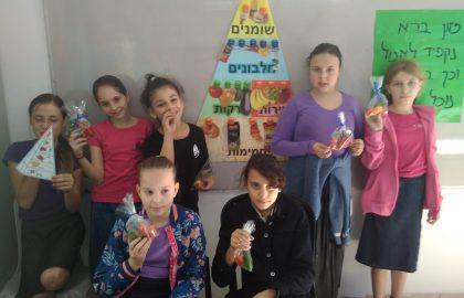 שיעור מדעים בכיתה ה' -פירמידת המזון שימו לב לשקית הירקות שבידי  הבנות!